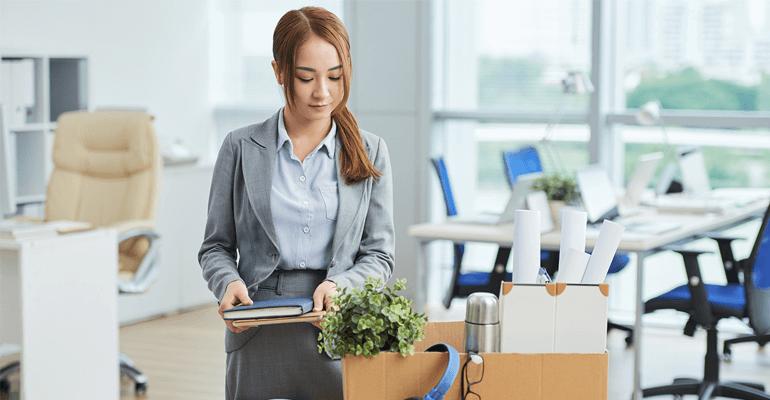 Mulher recolhendo os pertences de sua mesa após a demissão